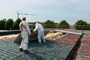 Painter uses high-pressure waterblaster on Asbestos roof